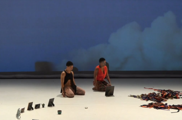 two Black dancers sitting with ancestor photos strewn about and video image of smoke stacks behind them; MBDance